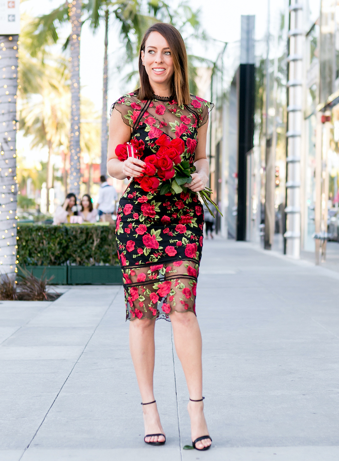 woman wearing black and red floral lace dress, black sandals, red dress for valentine's day, holding a bouquet of roses