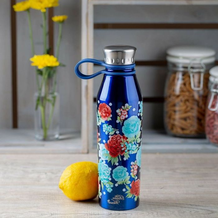 blue stainless steel water bottle, floral motifs drawn on it, romantic gifts for her, placed on wooden surface, lemon next to it