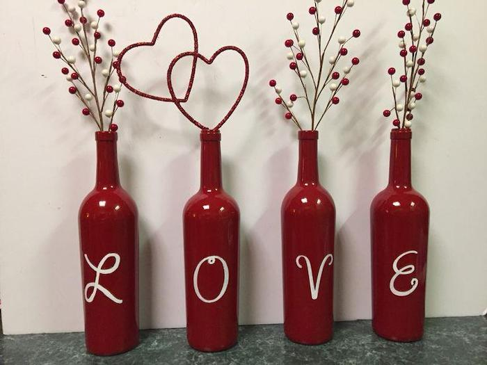 wine bottles painted in red, love spelled on them, filled with faux twigs in red and white, valentine's day decoration ideas