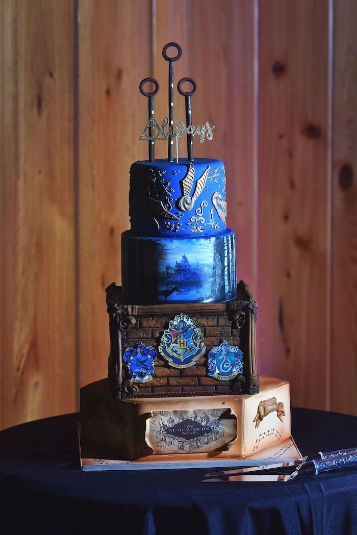 four tier cake, each layer with different image, hagrid birthday cake, ravenclaw inspired cake, marauder's map on bottom layer