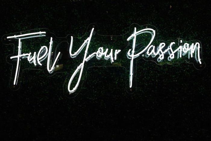 fuel your passion, white neon sign, hanged on greenery wall, aesthetic backgrounds, black background
