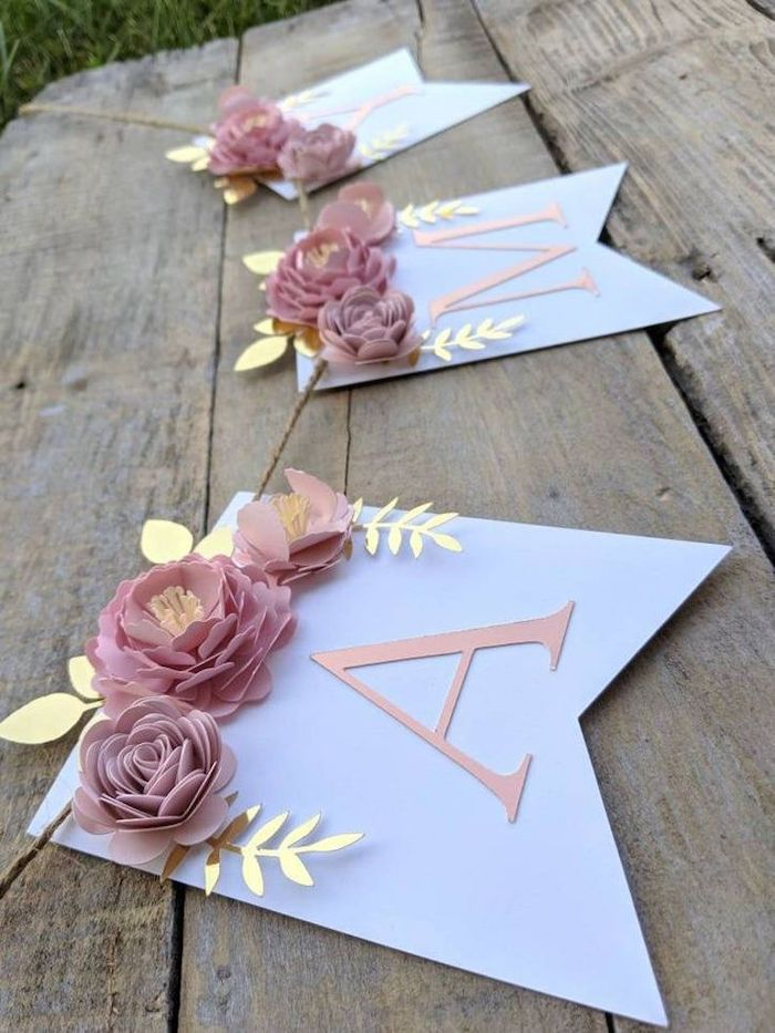 paper garland made with pink paper flowers, paper flower backdrop, placed on a wooden surface