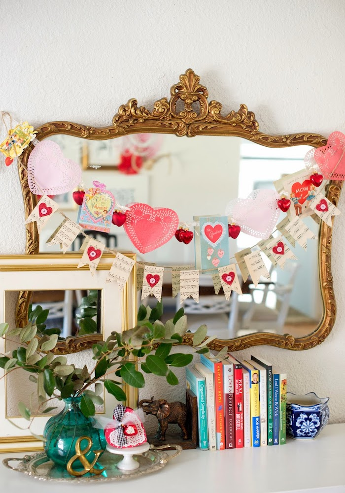 heart garlands hanging over vintage mirror, valentines day decor ideas, books and cases arranged on white surface