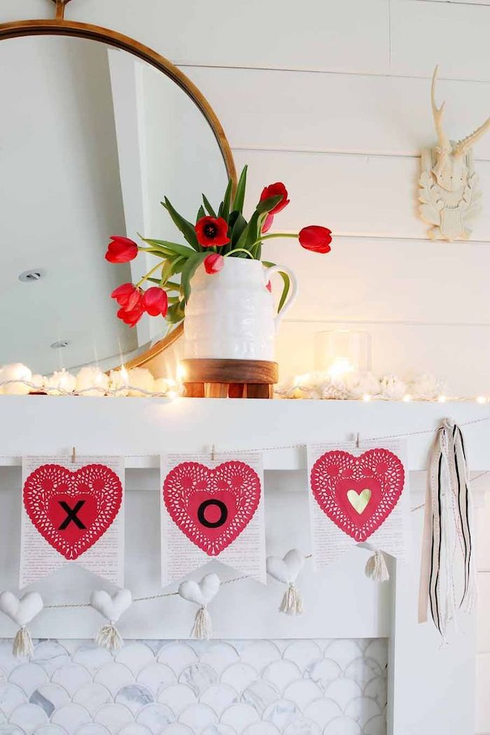 heart garland hanging over white mantel, valentines day decor ideas, lots of candles on top, bouquet of red tulips