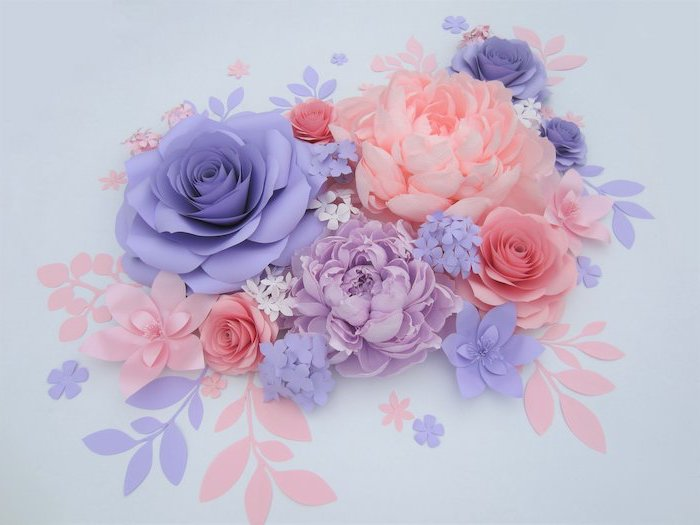giant paper flowers, purple blue and blush paper flowers, arranged together on white surface, different shapes and sizes