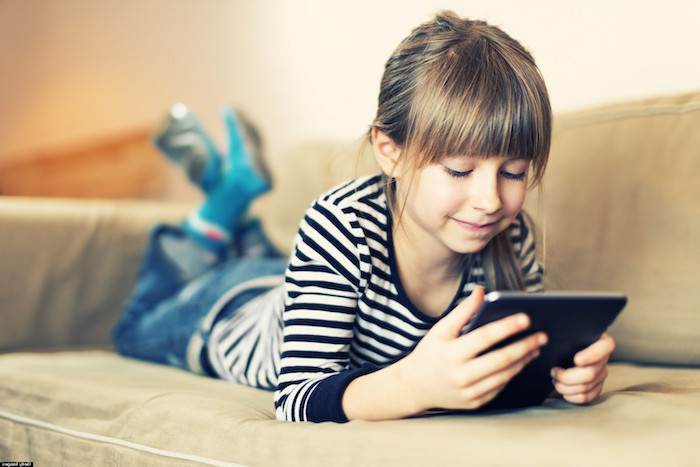 little girl lying on a sofa, holding a tablet, playing games, children's games, wearing jeans and black and white striped blouse