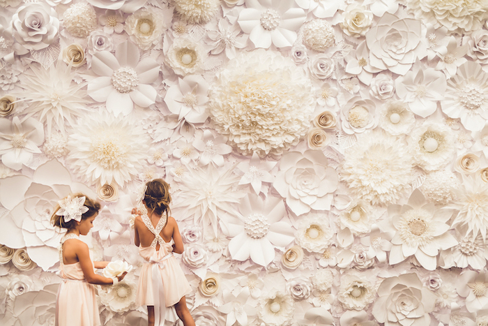 two girls wearing white dresses, standing in front of a large backdrop, covered with white paper flowers, giant paper flowers