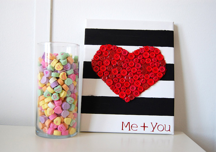 tall glass vase filled with conversation hearts, valentines day decor ideas, black and white striped poster, heart made of red buttons