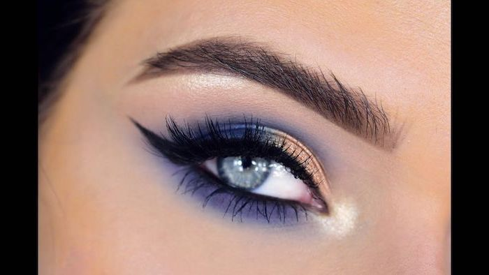 golden and purple blue eyeshadow colors, black cat eyeliner, green eyeshadow, woman with blue eyes and dark eyebrows