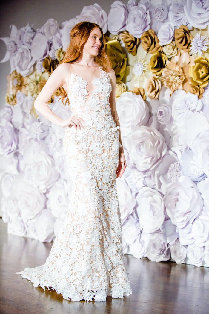woman with long red hair, wearing a white lace wedding dress, giant paper flowers, large backdrop with white and gold paper flowers