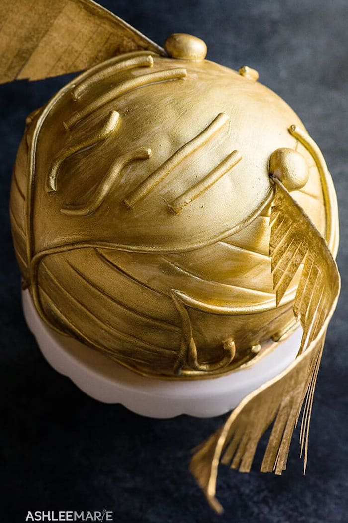golden snitch cake, placed on white cake stand, harry potter cake, step by step diy tutorial