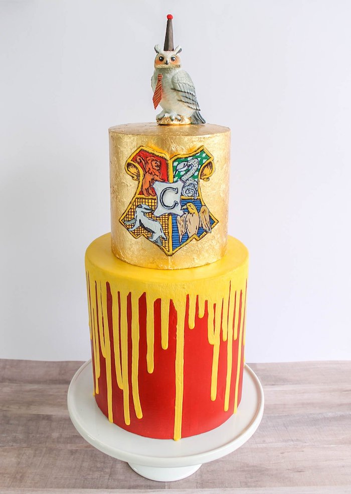 two tier cake, one gold tier with hogwarts symbol, hagrid cake, bottom gryffindor tier with red and yellow fondant