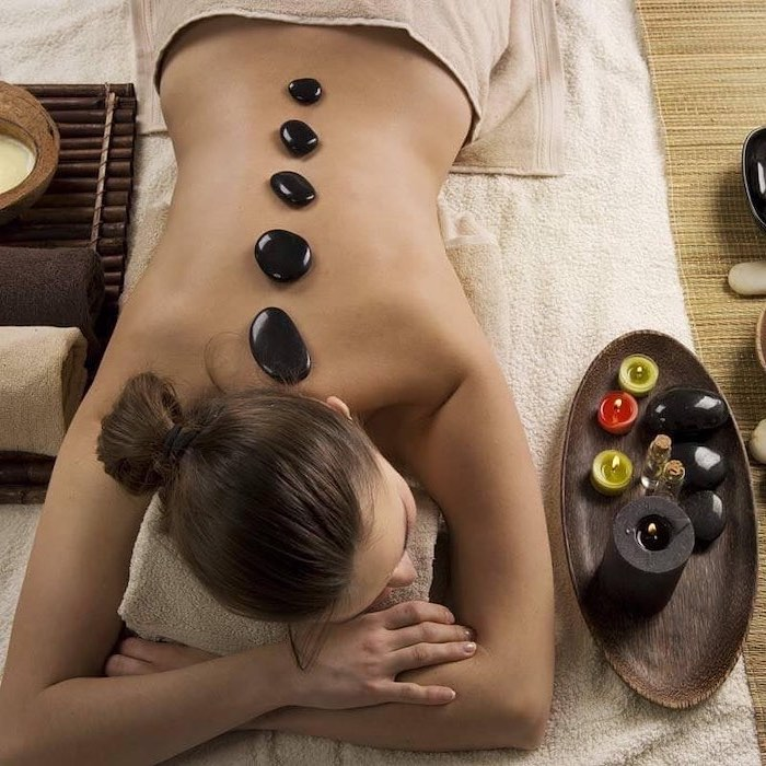 woman lying on towels, black rocks on her back, romantic gifts for her, spa treatement