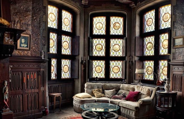 large windows in gothic style living room, grey sofa with throw pillows, stained glass doors, wooden fireplace