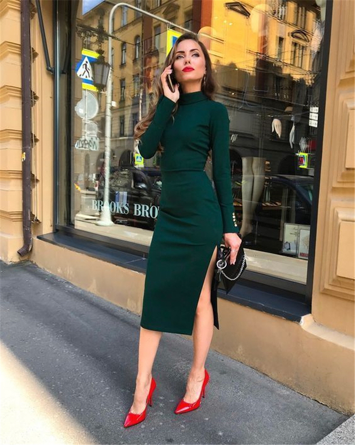 woman standing on sidewalk, wearing green dress with long sleeves, red heels and black bag, red valentines day dress