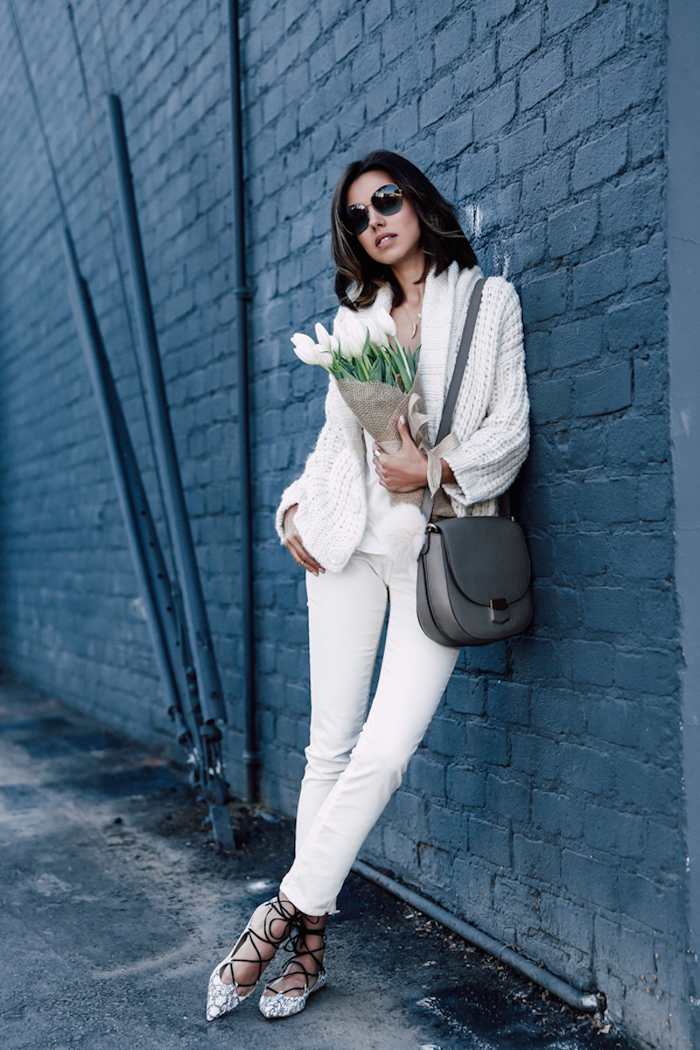 woman leaning on black brick wall, red valentines day dress, wearing white pants and cardigan, holding bouquet of tulips