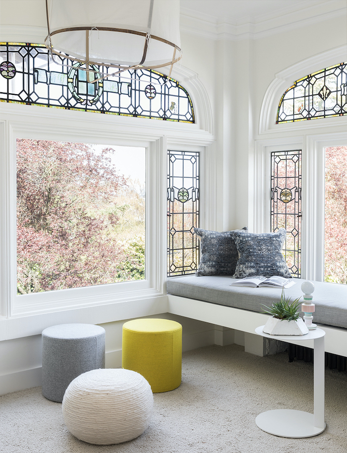 large windows, how to make stained glass, grey white and yellow ottomans, next to bench with grey throw pillows