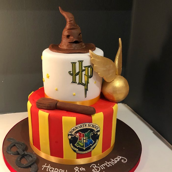 hagrid cake, two tier gryffindor cake, made with red and yellow fondant, sorting hat and golden snitch toppers