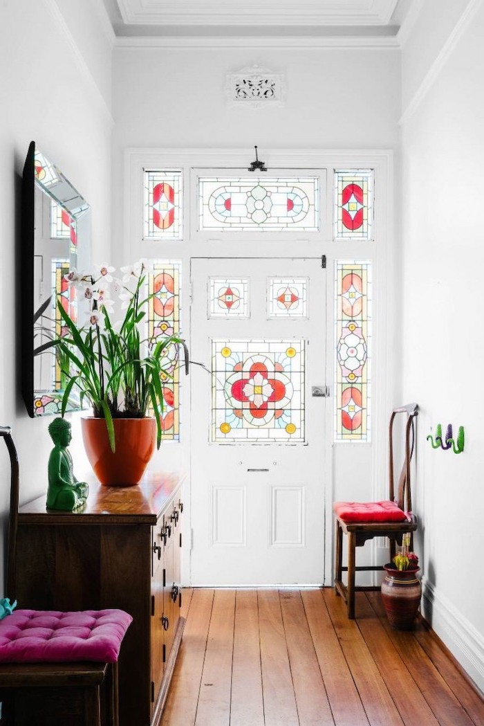 front door decorated with glass, stained glass doors, hallway with wooden floor, vintage wooden cabinet
