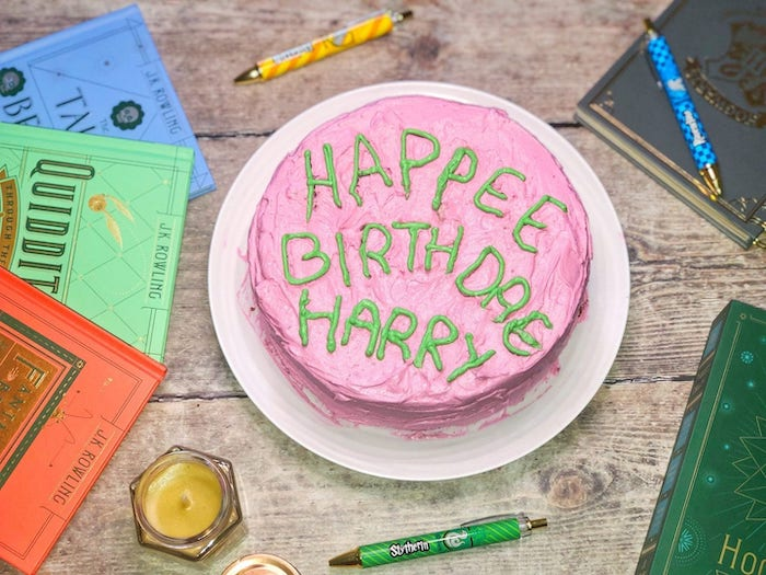 happee birthdae harry cake, covered with pink and green buttercream, hagrid cake, placed on wooden table