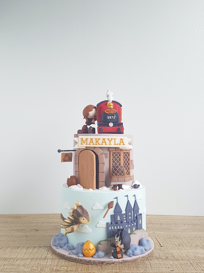 harry potter themed cake, two tier cake, portraying hogwarts and hut, hogwarts express and hermione on top