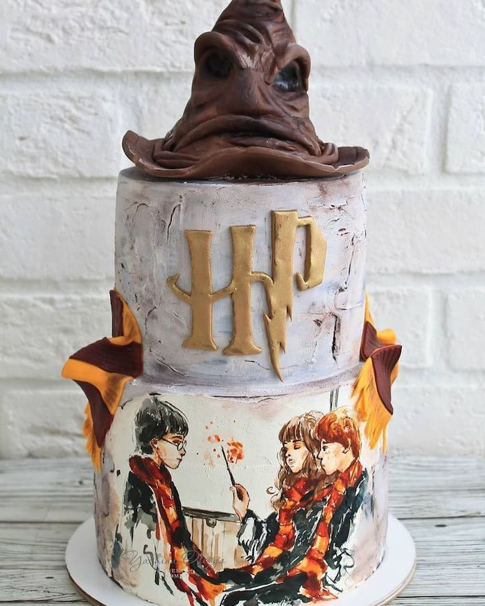 two tier cake with white fondant, harry potter themed cake, sorting hat on top, harry ron and hermione painted on the bottom tier