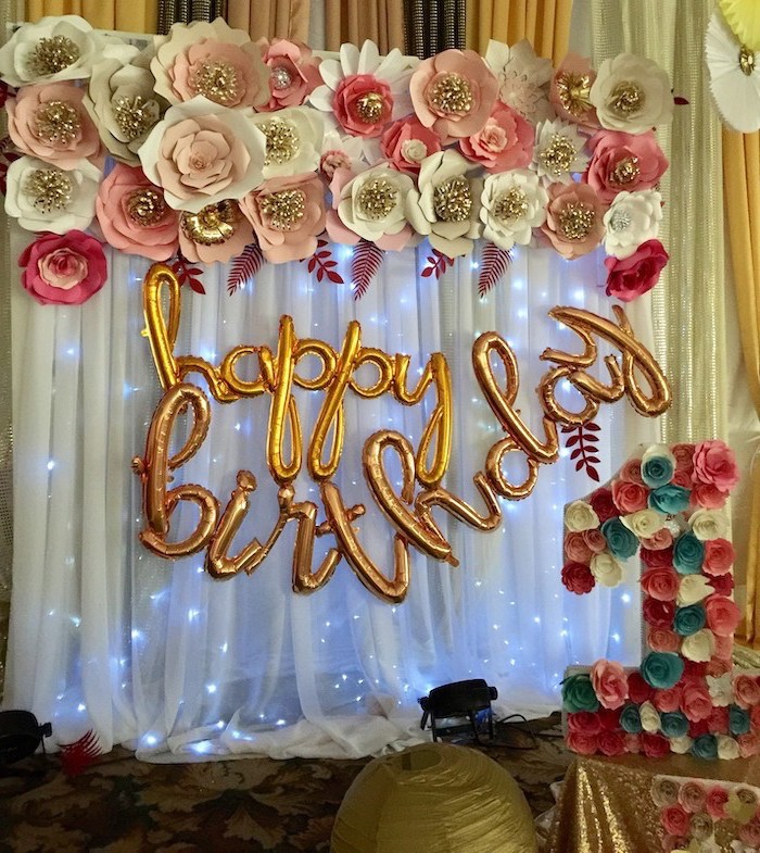 happy birthday balloons, hanging on white tulle with fairy lights, crepe paper flowers, paper flowers arranged on top