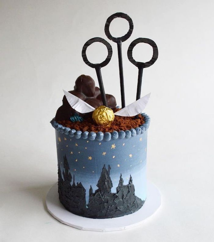 one tier cake with blue fondant, harry potter themed cake, qudditch hoops and golden snitch toppers, hogwarts drawn on it