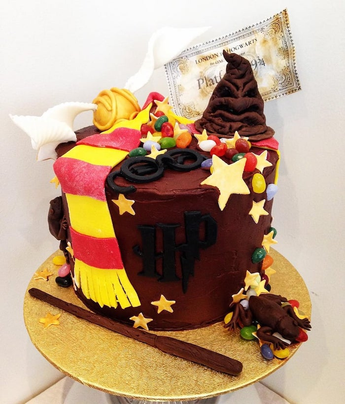 cake with brown buttercream, sorting hat and glasses, golden snitch and gryffindor scarf, made of fondant on top, harry potter themed cake