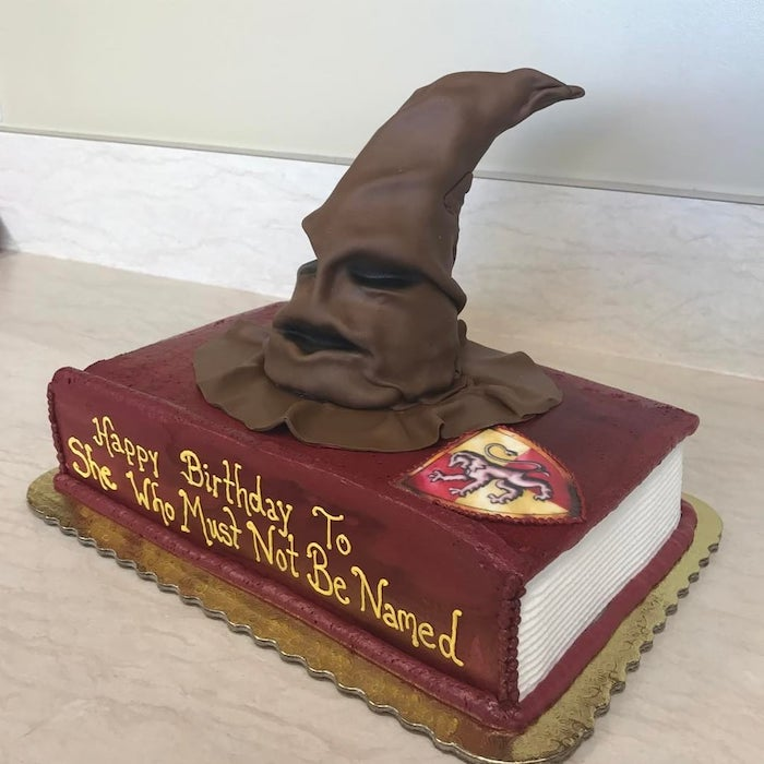 one tier cake in the shape of a book, harry potter themed cake, she who must not be named, sorting hat on top