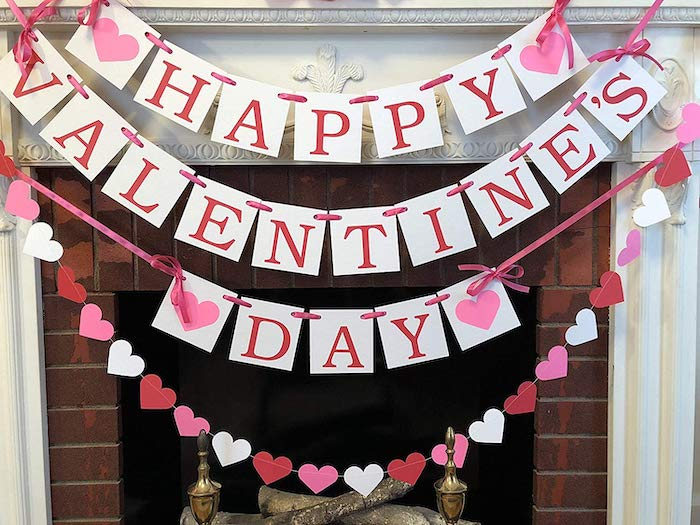 happy valentine's day banner, hearts garland hanging over mantel, tied with pink bows, valentines day decor ideas