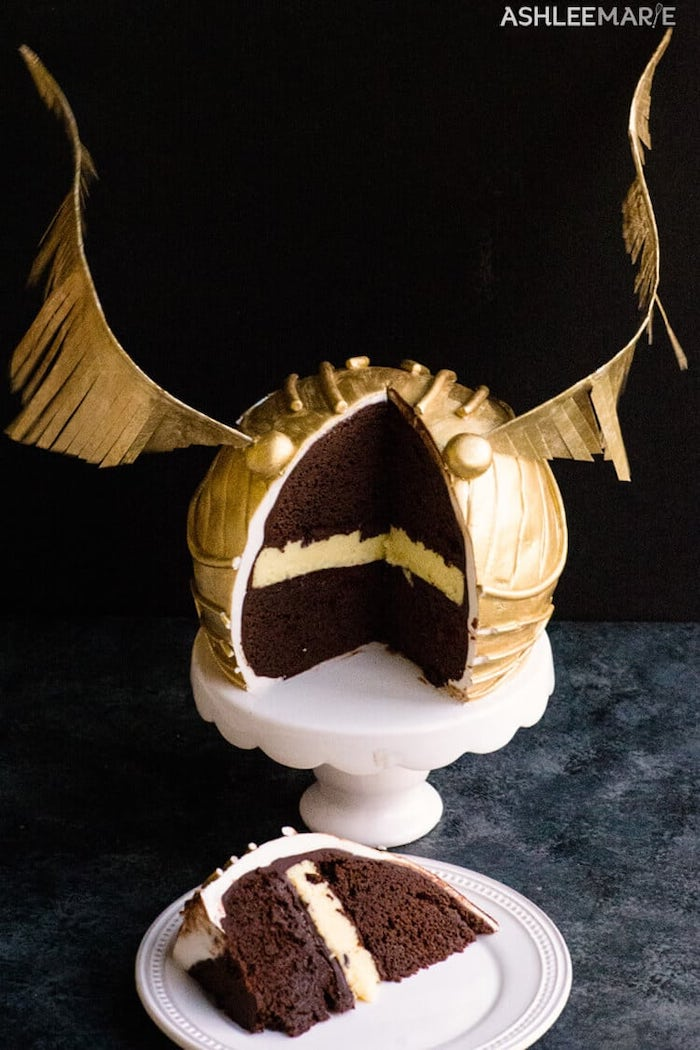 slice cut out of golden snitch cake, placed on white plate, harry potter birthday cake, black background