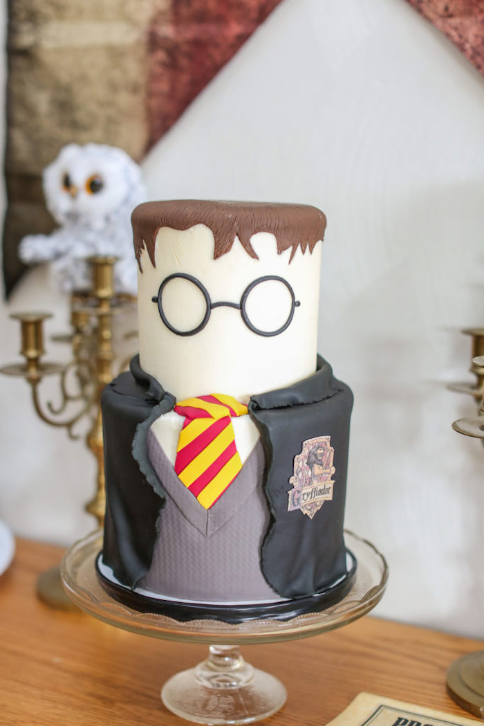 happy birthday harry potter cake, two tier cake, harry with gryffindor uniform, placed on glass cake stand