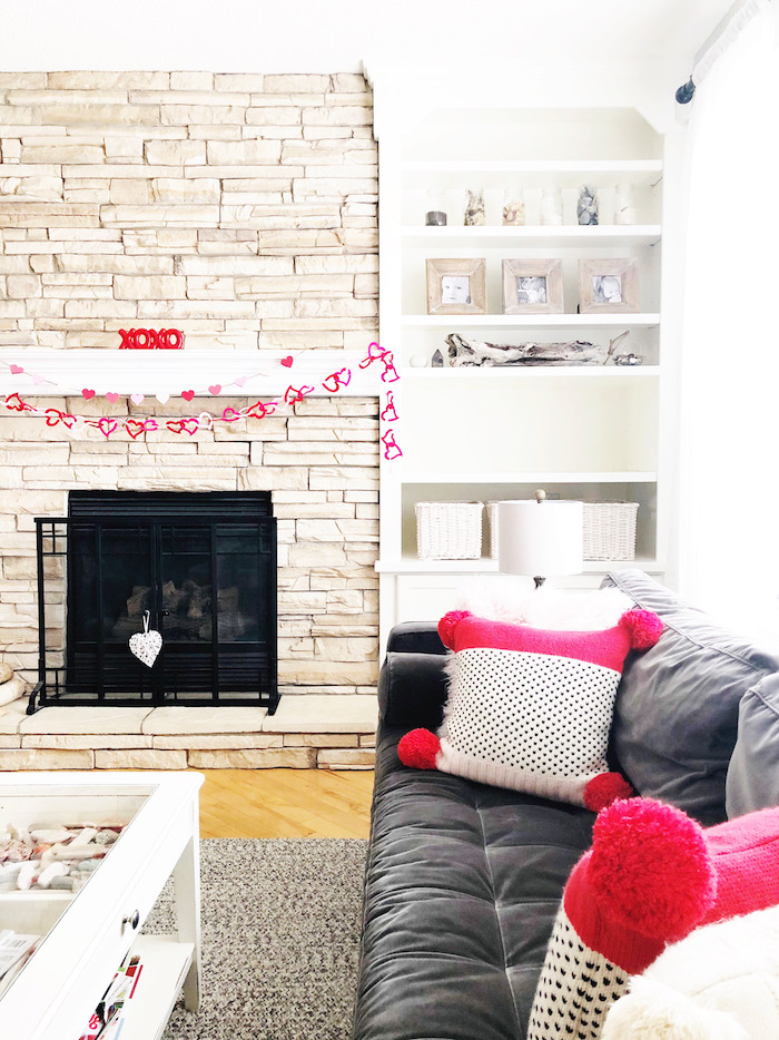 valentines day decor ideas, hearts garland hanging over mantel, pink and white throw pillows with black hearts, black velvet sofa