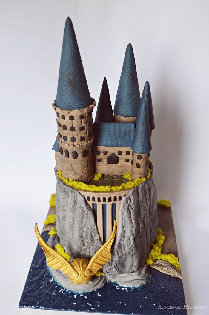 two tier hogwarts cake, harry potters birthday cake, golden snitch on the side, made with fondant, white background