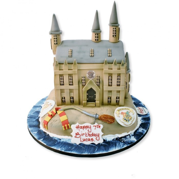 hogwarts cake made with fondant, harry potters birthday cake, broom and gryffindor scarf on the side, white background
