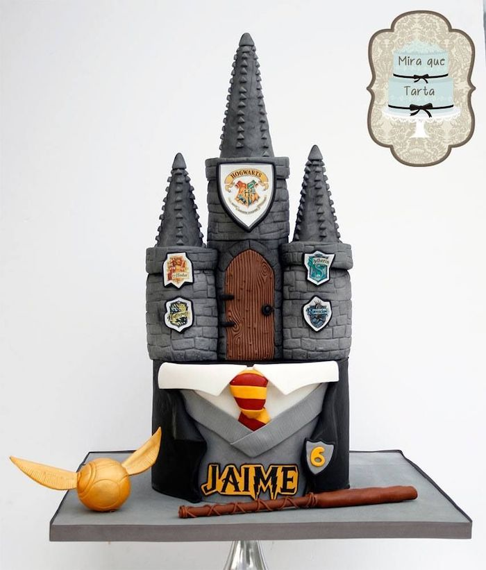 two tier hogwarts cake, harry potters birthday cake, gryffindor uniform, golden snitch and wand on the side