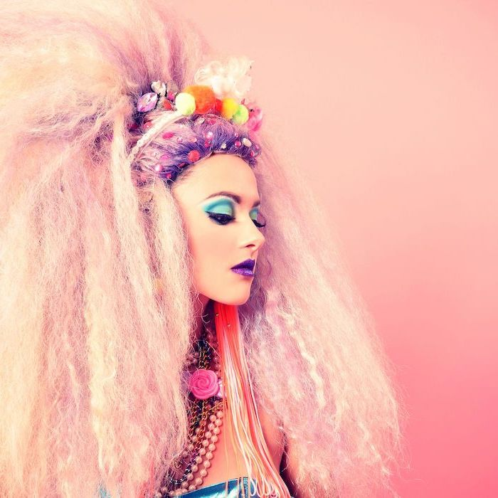 woman with blonde hair, turquoise blue eyeshadow colors, black cat eyeliner, dark purple lipstick, green eyeshadow