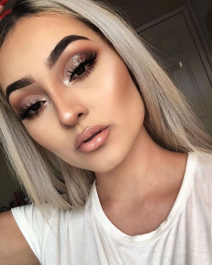 how to do eyeshadow, blonde woman with thick dark eyebrows, silver glitter eyeshadow colors, nude lipstick