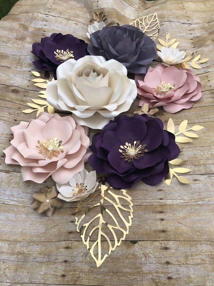 large white blush and purple paper flowers, different shapes and sizes, paper flower decorations, placed on wooden surface