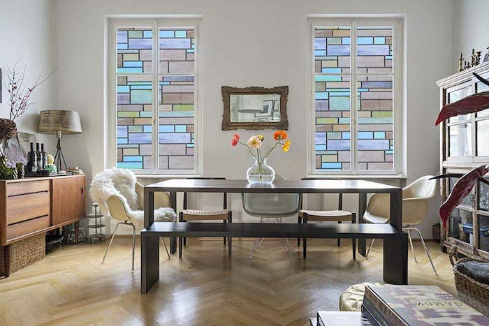 dining room with dark wooden table, white chairs and wooden floors, tall windows decorated, stained glass doors