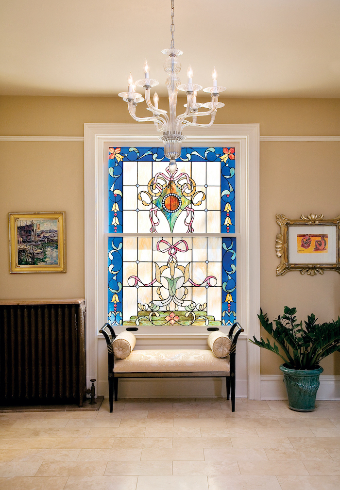 white ottoman in front of window, decorated with different colors, leaded glass, white tiled floor and glass chandelier
