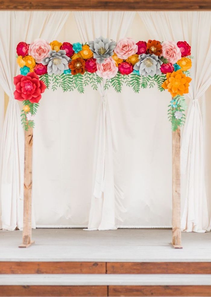 wooden arch, decorated with colorful paper flowers, paper flower decorations, white curtains in the background