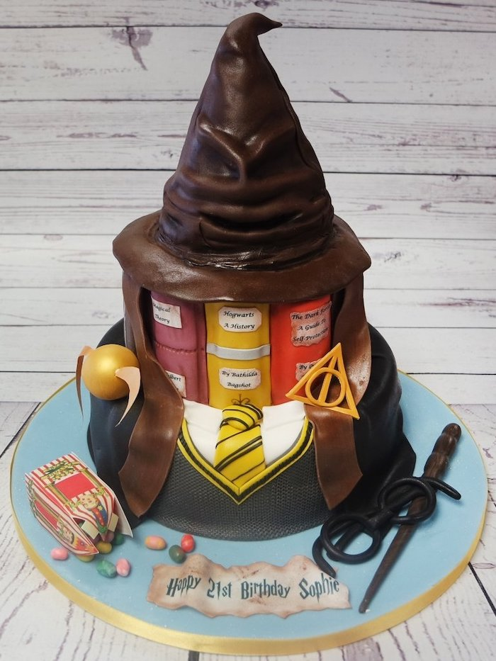 two tier cake, hufflepuff unidorm bottom tier, vooks second tier, sorting hat made of fondant on top, harrys birthday cake