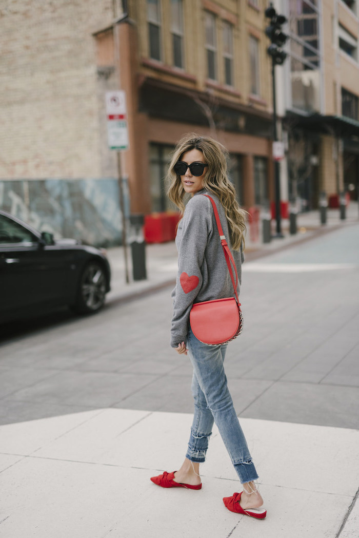 woman walking on sidewalk, wearing grey sweater and jeans, red shoes and bag, red valentines day dress