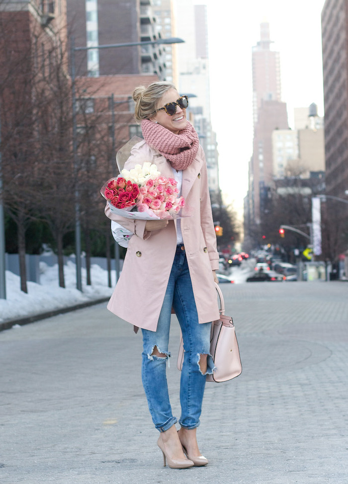 woman holding bouquet of roses, date outfit ideas, wearing jeans and white shirt, pink coat and scarf, nude shoes and bag