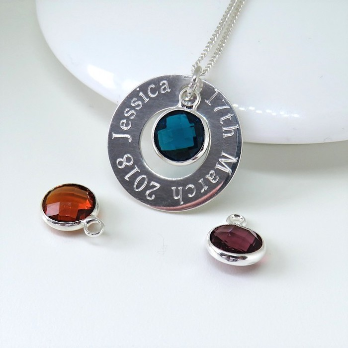 personalised silver necklace with birthstone in the middle, best valentines gifts for her, placed on white surface