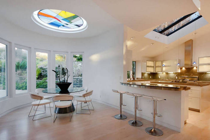 ceiling window decorated with colored glass, stained glass doors, dining room with glass round table, white chairs