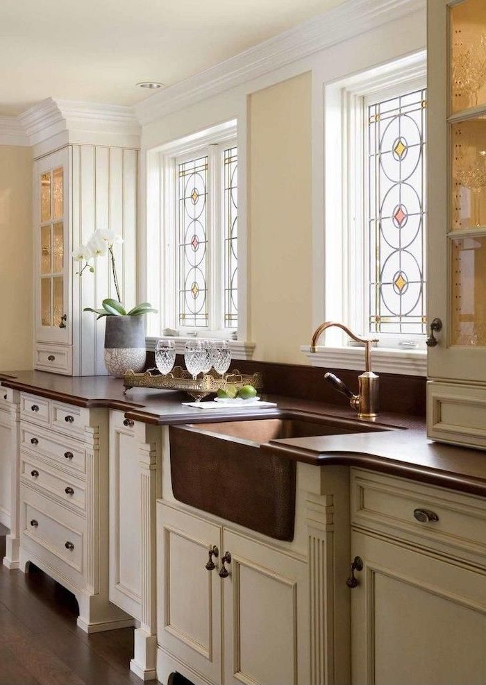 stained glass window hangings, kitchen with white cupboards, dark wooden countertops, large windows