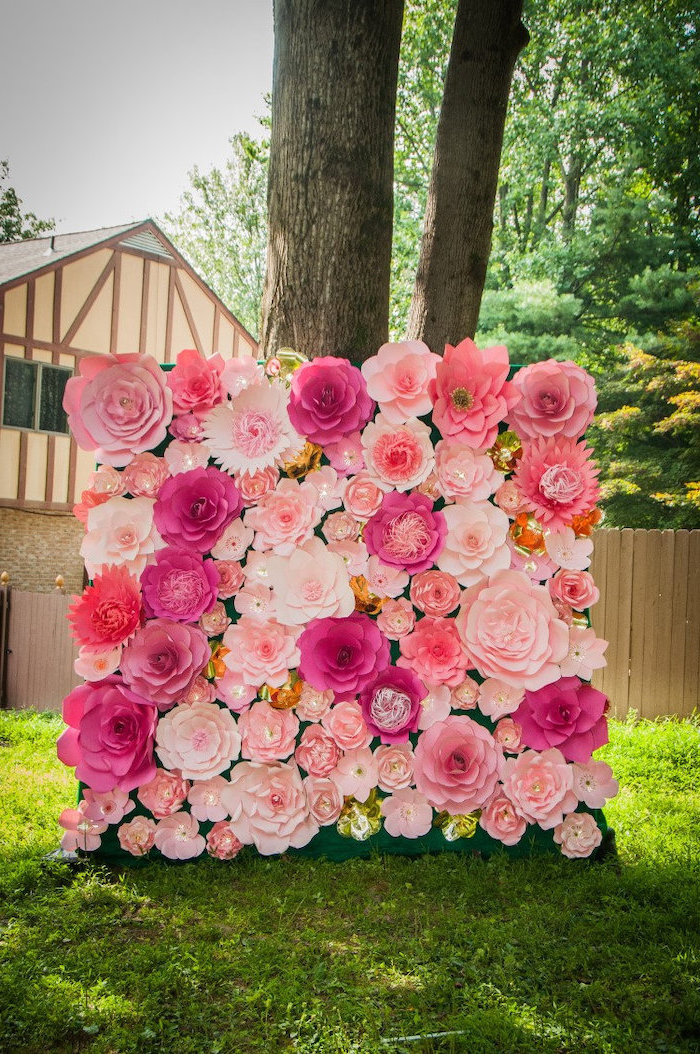 pink and blush paper flowers, arranged together as a backdrop, paper flower wall decor, placed on the ground